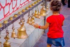 POKHARA, NEPAL PAŹDZIERNIK 10, 2017: Piękna mała dziewczynka dotyka dzwony różny wielkościowy obwieszenie w Taal Barahi Obraz Stock