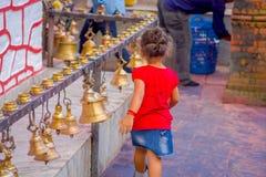 POKHARA, NEPAL PAŹDZIERNIK 10, 2017: Piękna mała dziewczynka dotyka dzwony różny wielkościowy obwieszenie w Taal Barahi Zdjęcia Stock