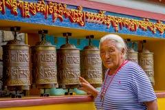 POKHARA NEPAL, PAŹDZIERNIK, - 06 2017: Portret niezidentyfikowana pilgrin kobieta dotyka modlenie toczy wewnątrz Tybetańską świąt Zdjęcie Stock