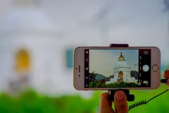 POKHARA, NEPAL, SEPTEMBER 04, 2017: Close up of a beautiful view of the temple in the screen of a smartphone with a Royalty Free Stock Photography