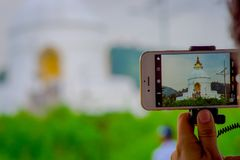 POKHARA, NEPAL, SEPTEMBER 04, 2017: Close up of a beautiful view of the temple in the screen of a smartphone with a Royalty Free Stock Photos