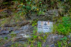 POKHARA, NEPAL, SEPTEMBER 04, 2017: Close up of informative sign over a metallic structure in a rock to visit the white Royalty Free Stock Photography
