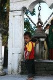 POKHARA, NEPAL. 25 September 2008: Little boy-Hindu pilgrim at a sacred bell at the temple of goddess Durga. royalty free stock photo