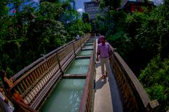 Pokhara, Nepal - September 12, 2017: Unidenfied people walking over the hanging long metal bridge over the Seti river. With high banks outside of Pokhara in Stock Photography