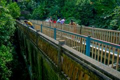 Pokhara, Nepal - September 12, 2017: Unidenfied peoplewalking over the hanging long metal bridge over the Seti river. With high banks outside of Pokhara in Stock Photo