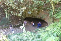 Pokhara, Nepal - September 12, 2017: Unidentified group of people at the enter of Bat Cave, with some vegetations Stock Photos