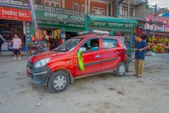POKHARA, NEPAL, SEPTEMBER 04, 2017: Unidentified man in gas station with his red car parked in dowtown near the Pokhara. Town in Nepal Royalty Free Stock Images