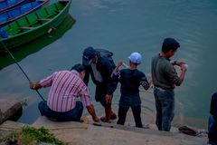 Pokhara, Nepal - September 04, 2017: Unidentified people fishing in lakeshore with some boats in the phewa lake in the. Water in Pokhara city, Nepal royalty free stock photo