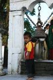 Pokhara, Nepal 25 September 2008: Weinig jongen-Hindoese pelgrim bij een heilige klok bij de tempel van godin Durga royalty-vrije stock foto