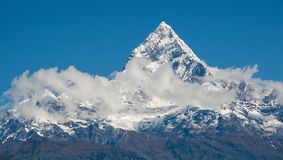 POKHARA, NEPAL: The Himalayas, Machapuchare Fishtail on the background of blue sky. POKHARA, NEPAL: Shooting from a bird`s eye view from a deltaplan. The stock photos