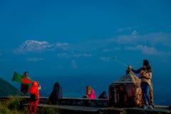 POKHARA, NEPAL, WRZESIEŃ 04, 2017: Niezidentyfikowani turyści przy szczytem Sarangkot punktu obserwacyjnego punkt, trzyma flaga i Obraz Stock