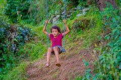 POKHARA, NEPAL, WRZESIEŃ 04, 2017: Piękna mała dziewczynka cieszy się parka w huśtawce wśrodku forets w Nepal Fotografia Royalty Free
