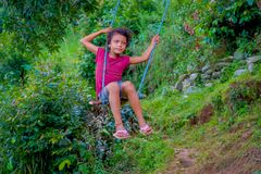 POKHARA, NEPAL, WRZESIEŃ 04, 2017: Piękna mała dziewczynka cieszy się parka w huśtawce wśrodku forets w Nepal Obrazy Stock