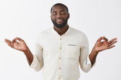 Pokojowa i zadowolona Afroamerykańska brodata męska czuciowa nirwana ono uśmiecha się od przyjemności medytująca z lotosową pozą  fotografia royalty free