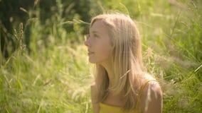 Pokojowa kobieta relaksuje w pięknym pogodnym outdoors patrzeje mądrze telefon zbiory
