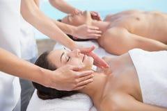 Pokojowa para cieszy się para masażu poolside Zdjęcie Stock