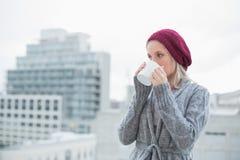 Pokojowa wspaniała blondynka pije kawę outdoors zdjęcie stock