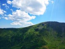 Pokojowe zielone góry zakrywać trawa pod jasnym niebieskim niebem Zdjęcia Stock