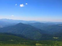 Pokojowe zielone góry zakrywać trawa pod jasnym niebieskim niebem Obraz Royalty Free