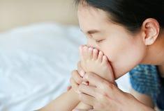 Pokojowi azjata matki całowania dziecka cieki na białym łóżku zdjęcie royalty free