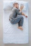 Pokojowy ładny mężczyzna stawia budzika na poduszce Obrazy Royalty Free
