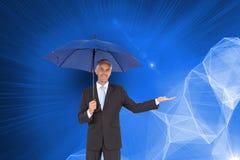 Pokojowy biznesmen trzyma błękitnego parasol Zdjęcie Stock