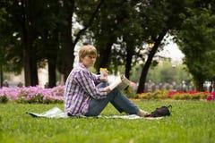 Pokojowy kobiety obsiadanie, czytanie i książka fotografia royalty free