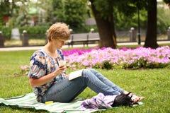 Pokojowy kobiety obsiadanie, czytanie i książka obrazy royalty free