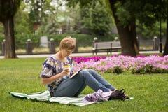 Pokojowy kobiety obsiadanie, czytanie i książka obraz royalty free
