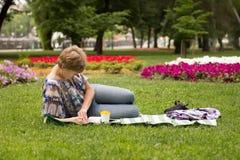 Pokojowy kobiety obsiadanie, czytanie i książka fotografia stock