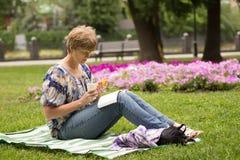 Pokojowy kobiety obsiadanie, czytanie i książka zdjęcie stock
