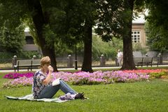 Pokojowy kobiety obsiadanie, czytanie i książka obrazy stock