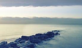 Pokojowy krzyż przetwarzał krajobrazowego wizerunek spokojny morze nad skałami Zdjęcie Royalty Free