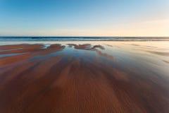 Pokojowy seascape: zmierzch na pływowej plaży Fotografia Stock