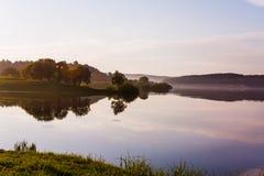 Pokojowy wieczór blisko jeziora w lecie Drzewa i niebo obrazy stock