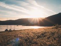 Pokojowy wschód słońca przy jeziorem: Żeglowanie łodzie cumować, spokojny nastrój zdjęcie royalty free