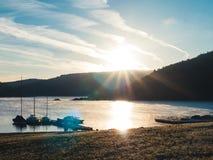 Pokojowy wschód słońca przy jeziorem: Żeglowanie łodzie cumować, spokojny nastrój zdjęcia royalty free