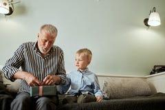 Pokolenie dziad i wnuk z prezenta pudełka obsiadaniem na leżance w domu obraz stock