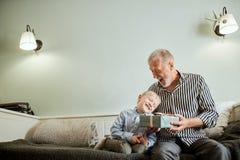 Pokolenie dziad i wnuk z prezenta pudełka obsiadaniem na leżance w domu obraz royalty free