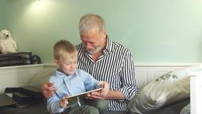 Pokolenie dziad i wnuk z prezenta pudełka obsiadaniem na leżance w domu zbiory