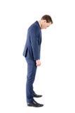 Pokonujący biznesmen patrzeje jego buty zdjęcie stock