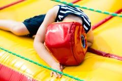 Pokonujący chłopiec lying on the beach w bokserskim hełmie fotografia stock
