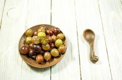 Pokrojeni jagodowi agresty Stubarwne jagody agresty na talerzu Glin naczynia Obrazy Stock