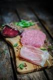 Pokrojeni prosciutto di Parma na drewnianej desce z salami i rosem zdjęcia stock