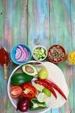 Pokrojeni warzywa na tortilla, składniki dla kulinarnych burritos graniczą z teksta terenem na drewnianym nieociosanym tło odgórn zdjęcie royalty free