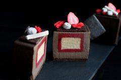 Pokrojona ciemna czekolada textured sześcianu deser z przyczepienie dekoracjami i czerwoną gąbką truskawkowymi i waniliowymi obrazy royalty free