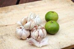 Pokrojona czosnku, czosnek goździkowej, czosnku żarówka, i zieleni cytryna na ciapanie bloku Obrazy Stock