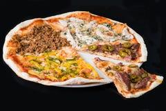 Pokrojona mięsna pizza na talerzu, ciemny tło Obrazy Royalty Free