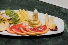 Pokrojona owoc na białym talerzu, winogrona, kiwi, pomarańcze, bonkreta Obrazy Stock