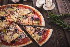 Pokrojona smakowita świeża pizza z pieczarkami i kiełbasą na drewnianym tle Obraz Stock